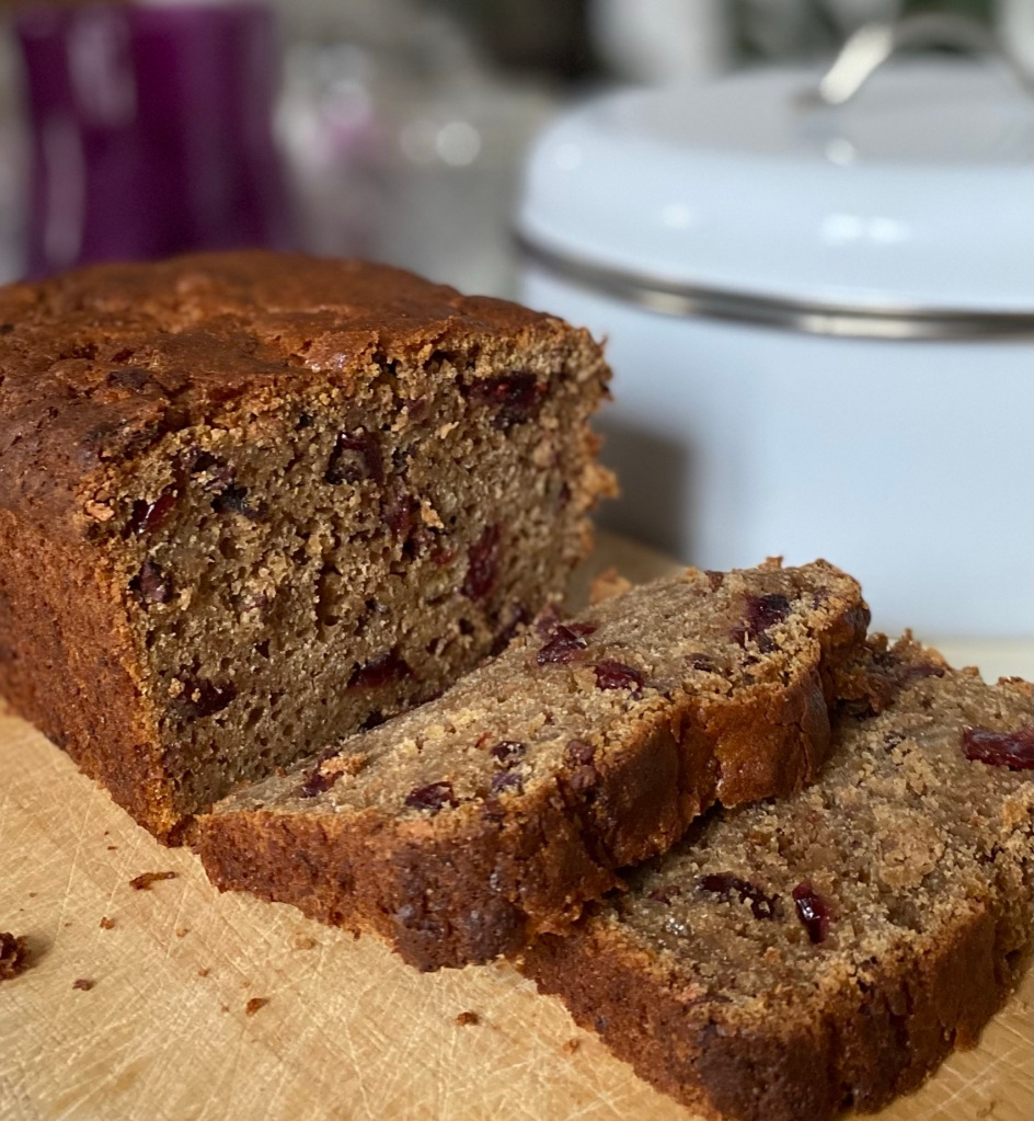 Healthy banana bread loaf with two cut slices on a board made with sourdough starter discard, cranberries and cacao nibs