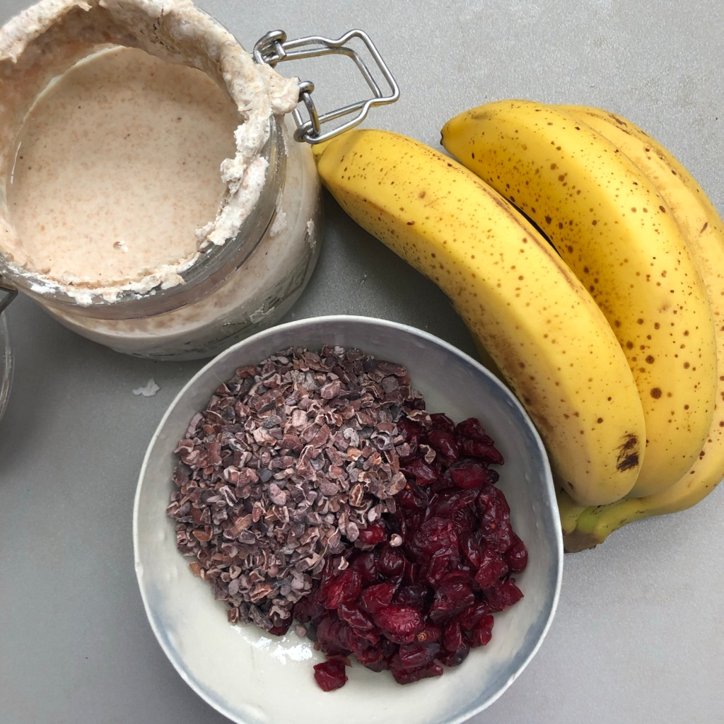 A pot of sourdough starter with some ripe bananas on a kitchen top next to cacao nibs and dried cranberries in a handmade bowl